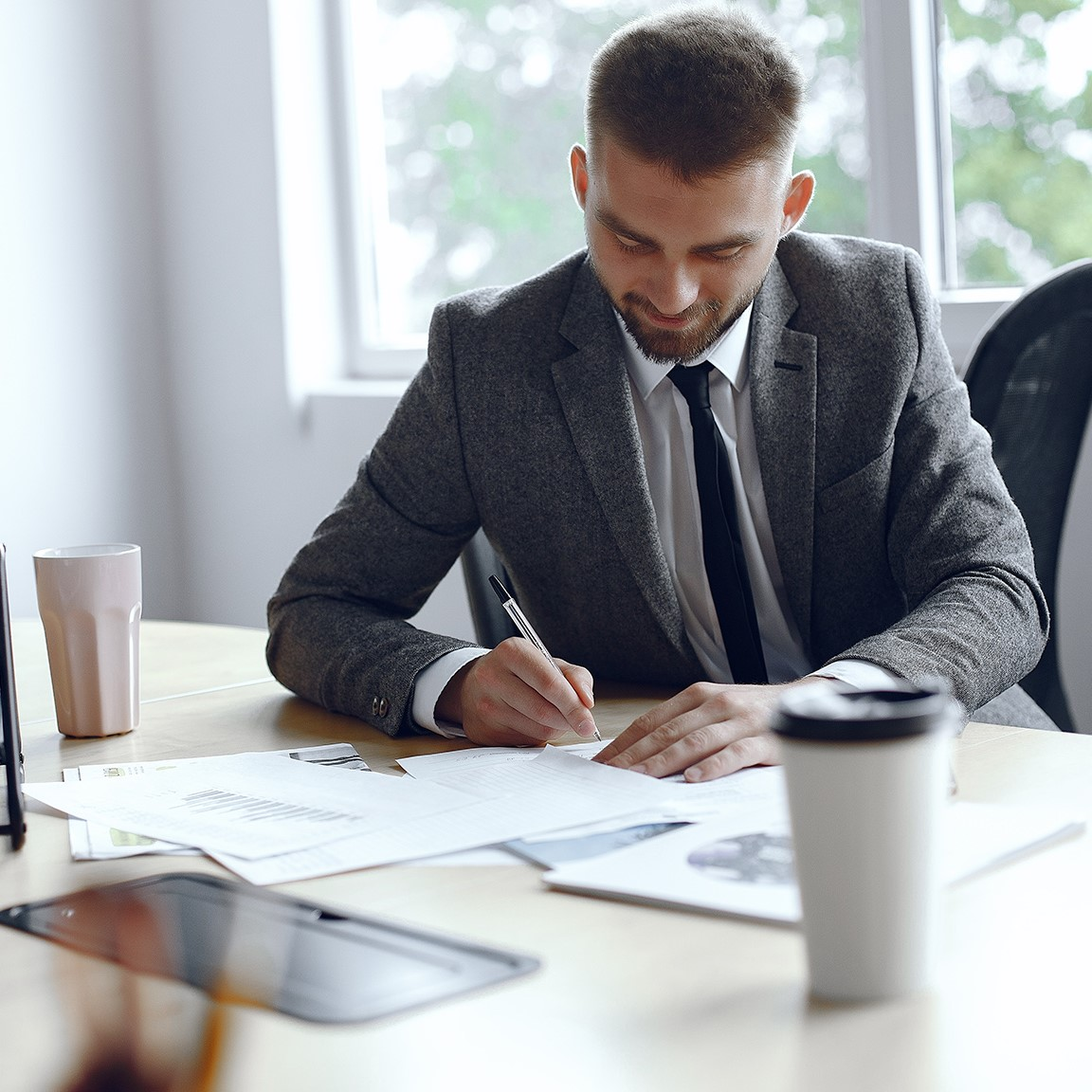 Man is sitting at the table. Guy in a business suit. Businessman  signs thedocuments